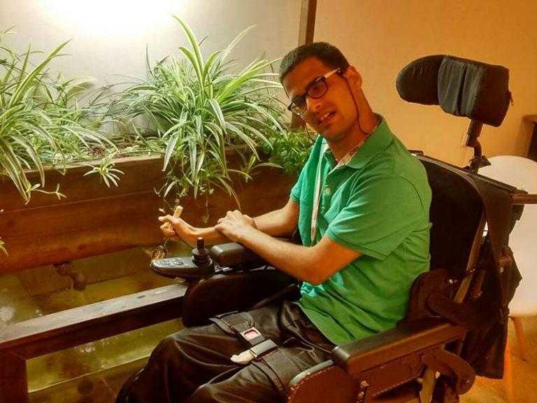 גבר בכסא גלגלים מטפל במערכת אקוופוניקה